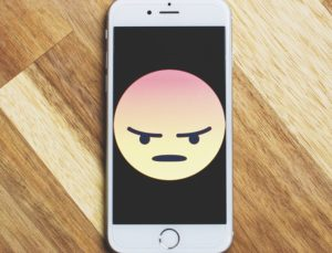 angry emoji on a phone meant to represent disparaging remarks.
