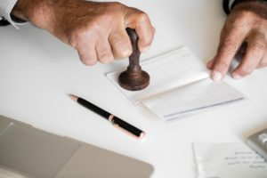 Image of older hands stamping a document.