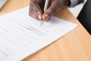 The hand of a man signing a document.