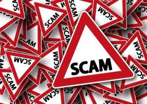"Signs reading ""scam"" to show the startling nature of debt collection scams."