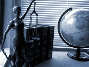 A justice statue next to a globe to illustrate how to execute an affidavit abroad.