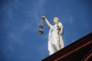 Statue of woman holding scales to represent new york debt collection laws.