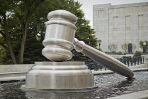 Image of a gavel in front of a court house to represent new york debt collection court